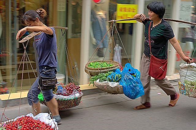 Chinese women are carrying basket. wikimedia
