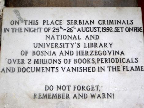 """La lapide nella Biblioteca di Sarajevo recita: """"Qui un gruppo di criminali serbi incendiarono la biblioteca nazionale e universitaria di Bosnia e Erzegovina nella notte tra il 25 e il 26 di agosto. Oltre 2 milioni di libri, riviste, documenti svanirono tra le fiamme. Non dimenticate, ricordate e state in guardia!"""""""
